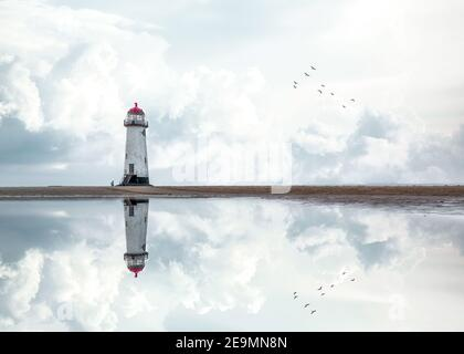 Lighthouse standing pool of water stunning dramatic storm clouds reflection reflected water sea steps Wales seashore sand beach still water pool - Stock Photo