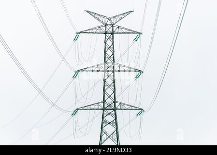 Extra-high voltage 400 kV overhead power line on large pylons, used for long distance, very high power transmission. Cloudy sky and copy space - Stock Photo