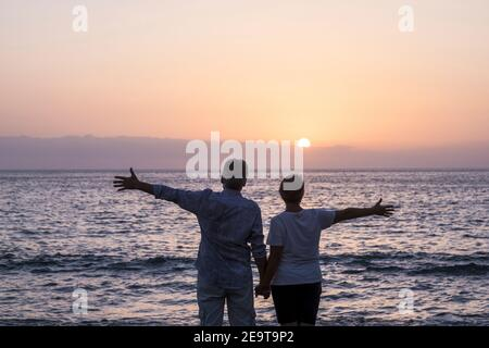 Happy senior couple people in love enjoy a sunset on the ocean holding hands - ñpve and relationship elderly summer holiday lifestyle man and woman to