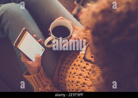 View of woman alone at home with coffee and phone connection online activity - people and lockdown coronavirus leisure indoor life - female use cellul