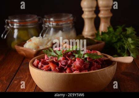 Vinegret or vinaigrette. Traditional Russian red salad with cooked and pickled vegetables, peas, beetroot, in wooden bowl on rustic background. - Stock Photo