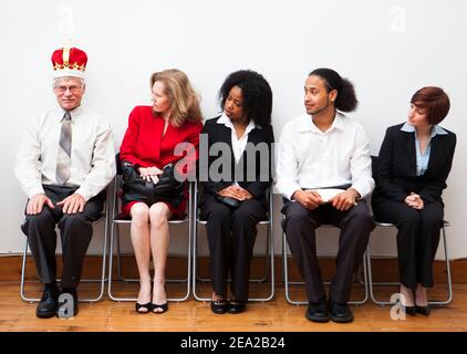 A group of prospective employees waiting for an interview. One man wears a crown to stand out from the rest. Humorous business concept.