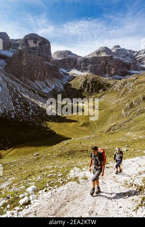 Hikers in the Zwischenkofel valley with the Antersasc alpine pasture below the Puez peaks in the morning sun, Dolomites Puez-Odle Group, South Tyrol