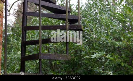 Outdoor black metal fire escape with bushes in the background - Stock Photo