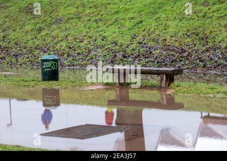 wooden bench in flooded grassland, dustbin nearby and reflection of people in water