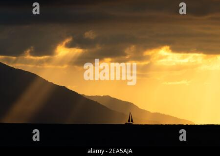 A Sailboat is Moving Along the Ocean as a Storm Looms and Sun Rays Break Through the Dark Clouds