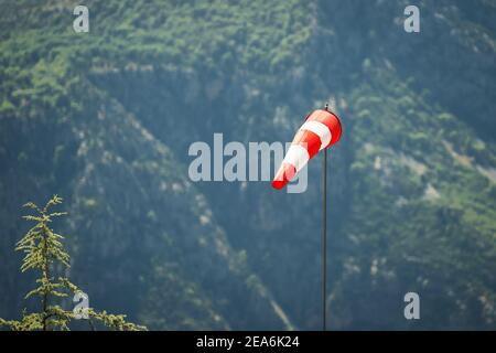 special sock with red and white stripes for measuring wind strength and direction is installed on airfields and runways for safety and weather detecti - Stock Photo