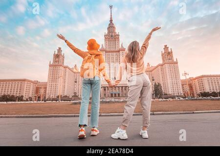 Two female friends students on the background of the building of Moscow University. Education, tourism and holiday concept - Stock Photo
