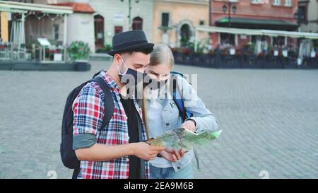 Two tourists in protective masks checking map on central city square, then admiring some beautiful place. Travel during the pandemic.
