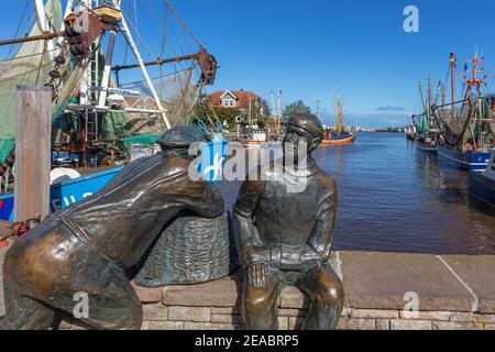 Fisherman monument old and young fishermen, shrimp cutters, in the port of Neuharlingersiel, East Frisia, Lower Saxony, - Stock Photo