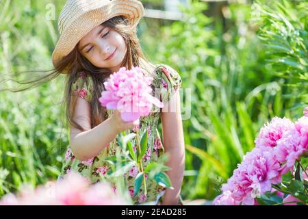 Beautiful little girl is holding a pink peony in a sunny day in the garden.  Pretty girl is wearing a fashionable patterned summer dress and straw hat