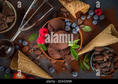 Dark Chocolate Ice cream. A lot of chocolate ice-cream with chocolate beans, powder and pieces, with icecream waffle cones and summer fresh berries on