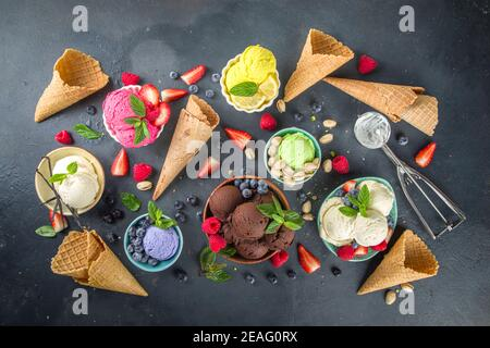 Various colorful ice cream balls in different bowls, with ice cream waffles cones and flavor ingredients - pistachio nuts, berries, lemon, chocolates,