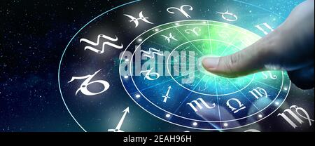 Astrological zodiac signs inside of horoscope circle. Man or Woman touching screen Zodiac signs hologram. Astrology concept.