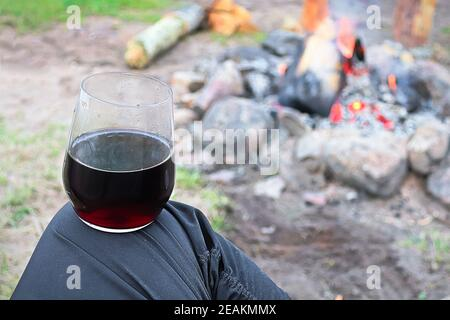 Balancing a glass of wine on a knee against a campfire
