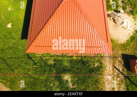 House with an orange roof made of metal, top view. Metallic profile painted corrugated on the roof.