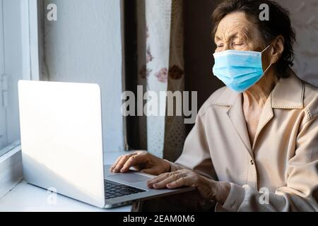 an elderly woman in a mask near the window with a laptop