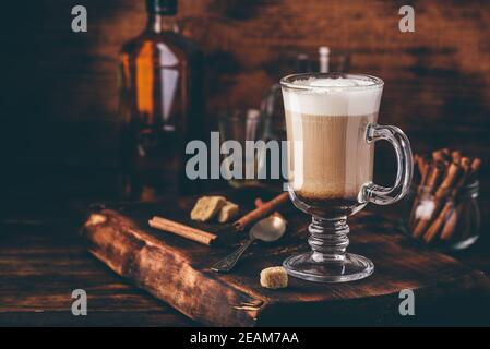 Coffee with Irish whiskey and whipped cream in glass