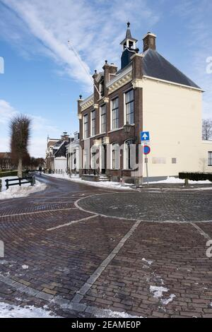 Former town hall in center of the city of IJlst, Friesland in the snow with blue sky Stock Photo