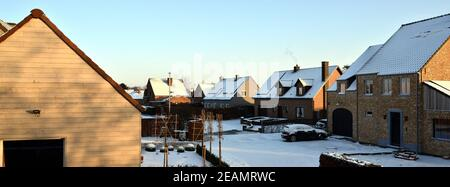 Typical Flemish suburb middle class detached houses with snow-covered roofs in a residential district. - Stock Photo