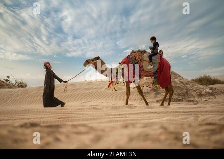 Tourist on camel back in inland sea