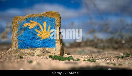 detail of a milestone representing the sign of the Way of St. James with an arrow and a yellow shell on a blue background