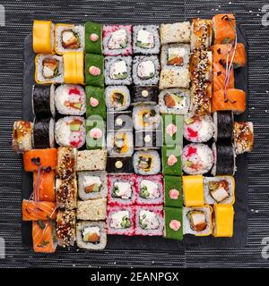 Japanese sushi food. Maki ands rolls with tuna, salmon, shrimp, crab and avocado. Top view of assorted sushi.