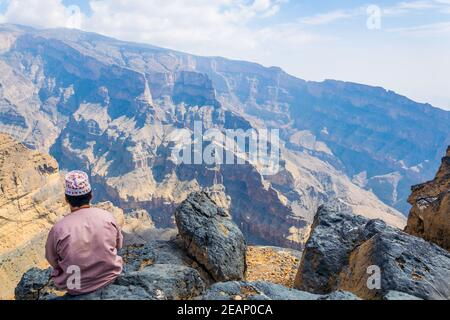 A man is sitting on the edge of 'the grand canyon of middle east' at the Jebel Shams mountain in Oman