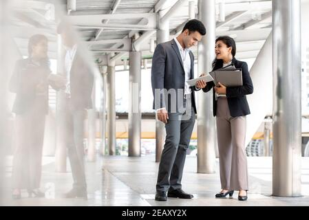 Indian businessman and businesswoman discussing work outdoors in city covered walkway