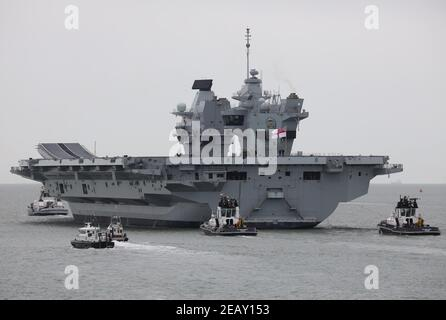 Tugs and security craft escort the Royal Navy aircraft carrier HMS PRINCE OF WALES into the Solent Stock Photo