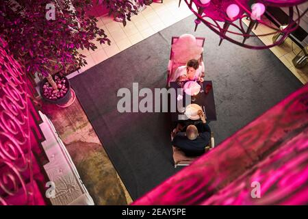 Romantic couple with champagne glasses sitting in a restaurant - Stock Photo