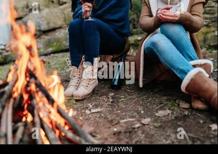 Unrecognizable women holding glass of red wine in campfire warming next to a fire.