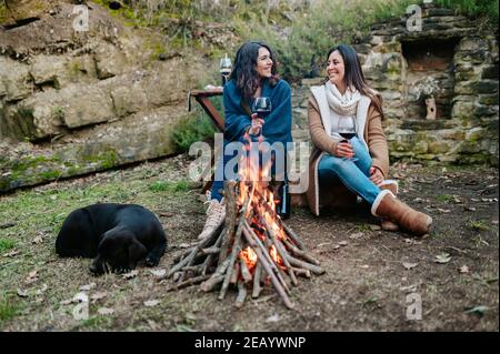 young happy women talking together while drinking glass of red wine. Females warming next to the fire with dog resting. Campfire, outdoors activities