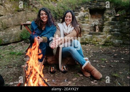 young happy women talking together while drinking glass of red wine. Females warming next to the fire. Campfire, outdoors activities concept.