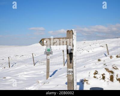 Pennine Way sign on wooden post snow covered moors and blue sky