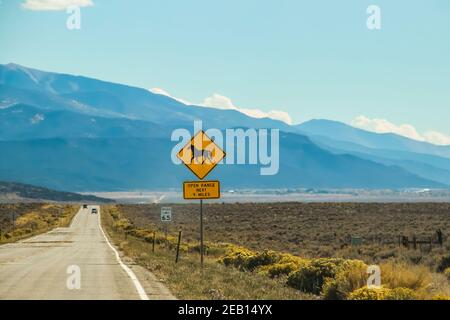 A heat shimmer on the road and cars in the high desert with mountains in the distance and a sign with a horse that says Open Range