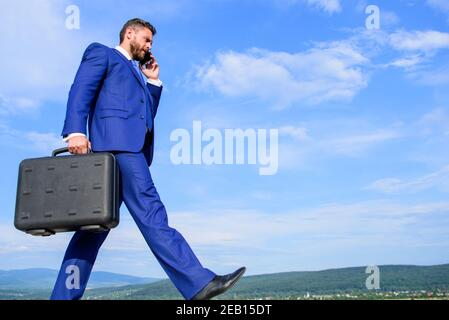 Keep going towards your goal. Businessman formal suit carries briefcase sky background. Businessman solving business problems on phone. Never stop. Entrepreneur in motion purposeful expression.