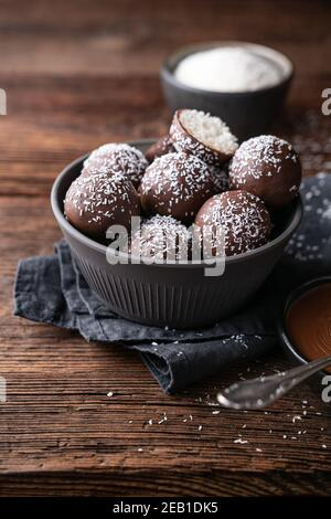 No bake delicious candy, sweet coconut balls dipped in chocolate on rustic wooden background