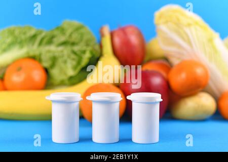 Bottles with food nutrition supplements in front of fruits and vegetables in blurry blue background - Stock Photo