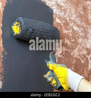 paint the wall with a roller,home renovation concept
