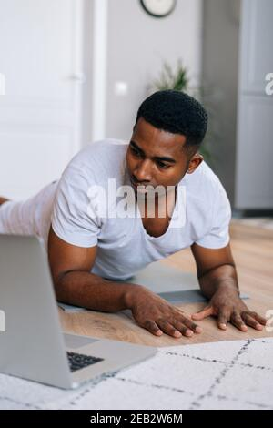 Close-up of young African-American man exercising workout in horizontal plank position using laptop