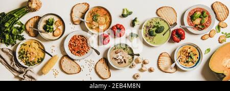 Flat-lay of vegetarian creamy homemade soup in plates with bread slices over white plain table background, top view. Autumn Winter creamy vegan soups, vegetarian food menu, comfort food concept