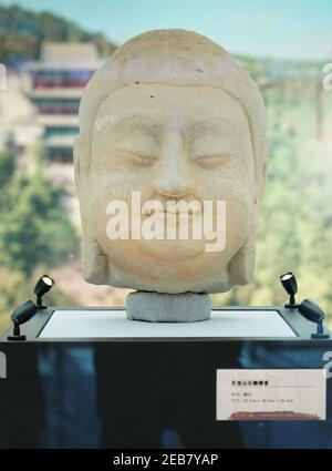 (210212) -- BEIJING, Feb. 12, 2021 (Xinhua) -- Photo taken on Feb. 12, 2021 shows a stone Buddha head of a statue in Cave 8 of the Tianlongshan Grottoes during an exhibition at Luxun Museum in Beijing, capital of China. A stone Buddha head that was stolen from China almost a century ago and recently retrieved has appeared at an exhibition at Beijing Luxun Museum starting from Friday, which is the Chinese Lunar New Year. The Buddha head belongs to one of the many stone statues in north China's Tianlongshan Grottoes, in the city of Taiyuan in Shanxi Province. It was the 100th relic retrieved