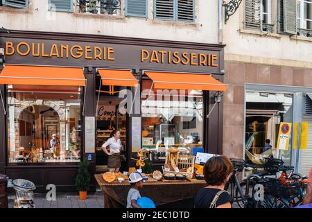 Strasbourg, France - July 29, 2017: Happy smiling woman in front of her stall selling multiple bakery products and traditional alsatian sweets in front of Boulangerie Patisserie large showcase