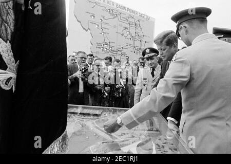 Trip to Western States: Pierre, South Dakota (Oahe Dam), 10:25AM. President John F. Kennedy views U.S. Army Corps of Engineersu0027 displays during the dedication ceremony of the Oahe Dam and Reservoir, on the banks of the Missouri River, near Pierre, South Dakota. Missouri River Division Engineer, Brigadier General Robert F. Seedlock, stands left of President Kennedy; Omaha District Engineer, Colonel Harry G. Woodbury, Jr. (back to camera), stands at right in foreground. Also pictured: Newsreel photographer for United Press Movietone, Thomas J. Craven, Sr.; White House Secret Service agents, - Stock Photo