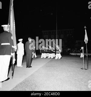 President Kennedy views the Marine Corpsu0027 Evening Parade, at the Marine Barracks Washington, D.C. (8th u0026 I Streets, SE), 9:00PM. President John F. Kennedy (back to camera) watches members of the Marine Corps Color Guard march during an evening parade at the Marine Barracks (u201c8th u0026 Iu201d) in Washington, D.C. Commandant of the United States Marine Corps, General David M. Shoup (wearing white), stands next to President Kennedy. - Stock Photo
