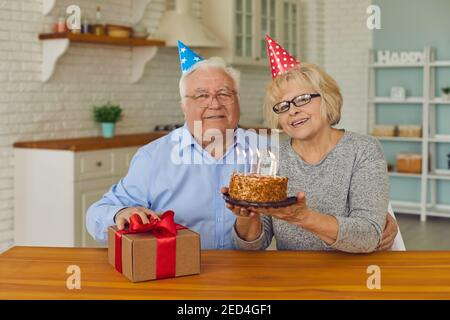 Smiling happy senior couple in clown festive hats sitting with birthday cake and gift box