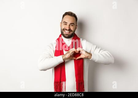 Christmas holidays and New Year concept. Happy father showing heart sign and smiling, I love you gesture, wearing winter sweater and scarf, white