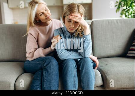 Worried mature mother consoles her adult daughter, helping with problem and depression, caring she, empathy, support in two age generations. Support of a loved one