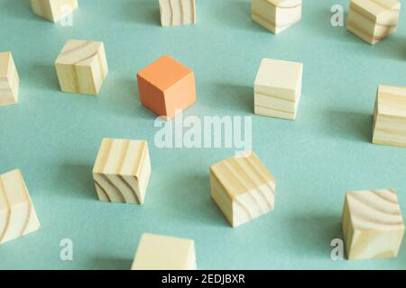 Group of wooden blocks and one different color block on green background. Different opinion, direction, idea, innovation concept